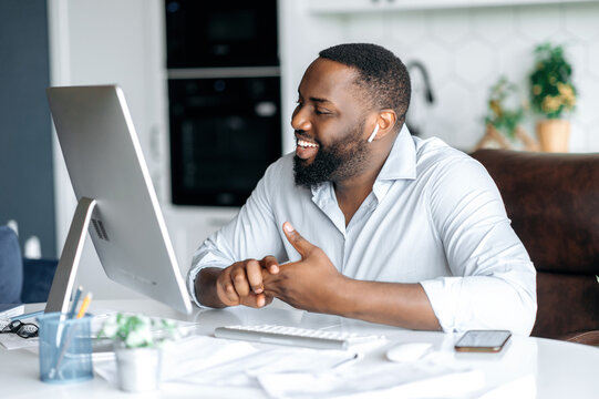 Joyful pleasant successful african american man, lawyer or real estate agent working remotely at computer, talking to colleague or customer via video call uses wireless headset, smiling friendly