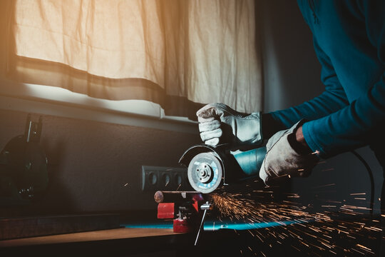 hands holding a circular saw cutting an iron bar with sparks jumping