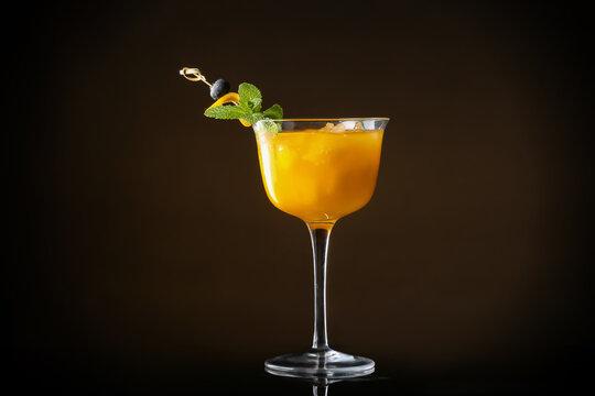Glass of tasty mango margarita on dark background