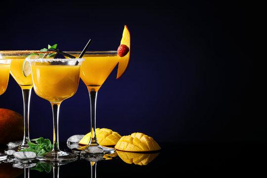 Glasses of tasty mango margarita on dark  background