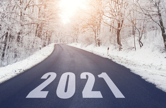 Empty road in forest in winter with 2021 text