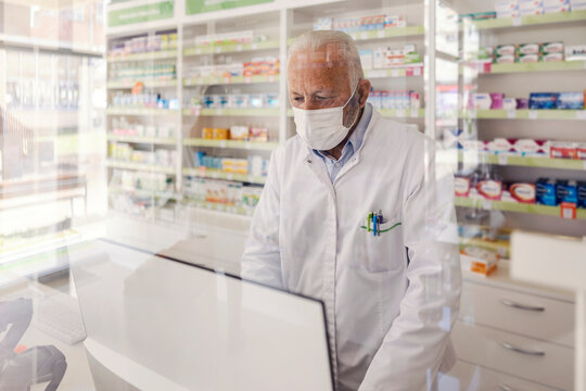 Pharmacist at the counter. A mature man in a white uniform and with a protective face mask on his face focused on working at a computer. A man at work, a pharmacist working during corona virus