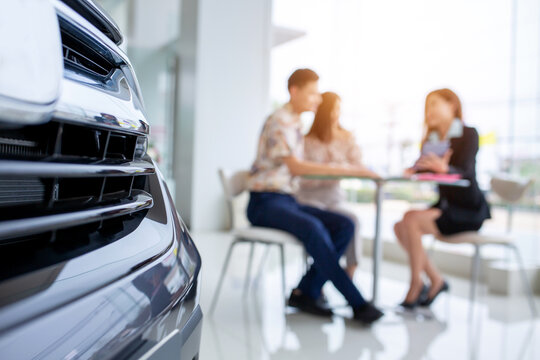 Selective focus on a new car and blur the dealership professional salesman negotiate and present. concept professionalism agreement contract leasing renting retail car sales