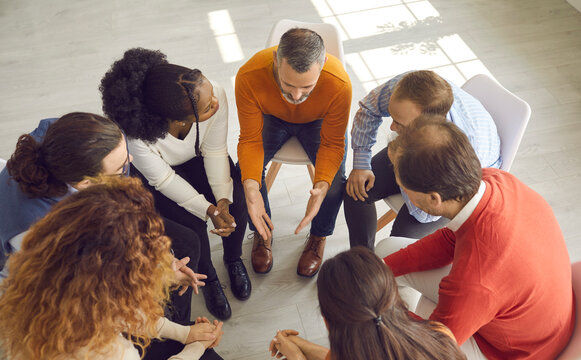 View from above of diverse people talking and supporting each other in group therapy session. High angle shot of multiethnic business team discussing important project in office meeting