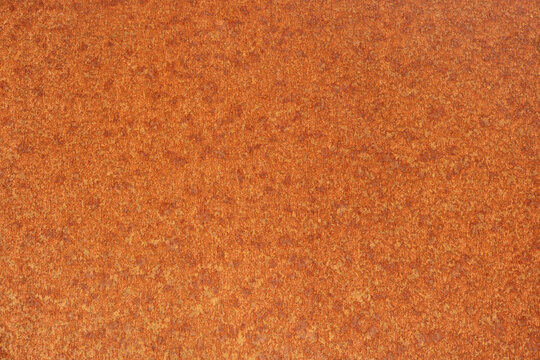 rusty orange surface pattern with corrosion effect on a metal iron board - old oxide regular texture for a background like sunspots