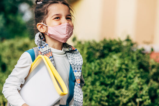 Portrait of a joyful kid wearing a pink protective face mask going to the school during coronavirus. Smiling little girl school student with backpack walking on the street.