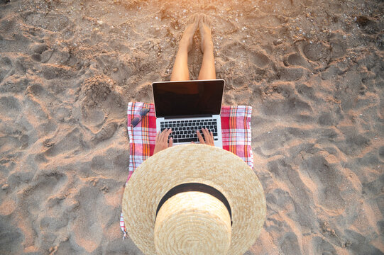 Young caucasian woman freelancer in a thatched sits on a sandy beach by the sea at sunset with a laptop and performs remote work or internet surfing. View from above