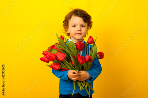 little cute boy with a blue jacket and a butterfly with a bouquet of tulips. A child holds a bouquet of flowers for his mother on Mother's Day