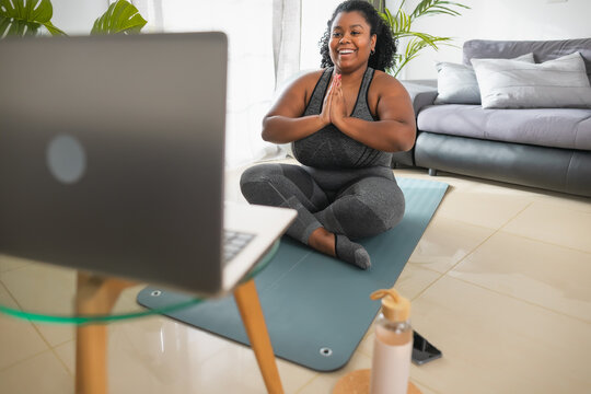 African young woman doing yoga virtual fitness class with laptop at home - E-learning and people wellness lifestyle concept