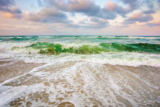 sea tide on a cloudy sunset. green waves crashing golden sandy beach. storm weather approaching. summer holiday concept