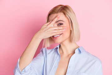 Photo of attractive happy young cheerful lady cover face hand smile isolated on pastel pink color background