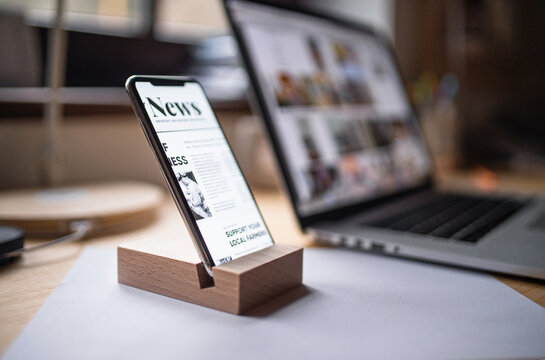 Smartphone in wooden stand holder on table indoors at home or on office.