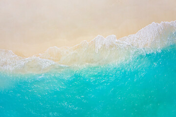Top view on coast waves on beach aerial view, crystal clear water. Stunning summer landscape, sunny tropical island shore. Seaside, idyllic nature Earth view. Stunning scenery, amazing view