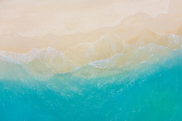 Fototapeta Top view on coast waves on beach aerial view, crystal clear water. Stunning summer landscape, sunny tropical island shore. Seaside, idyllic nature Earth view. Stunning scenery, amazing view