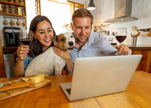 Happy couple with pet dog online celebrating winter holidays virtually with friends and family