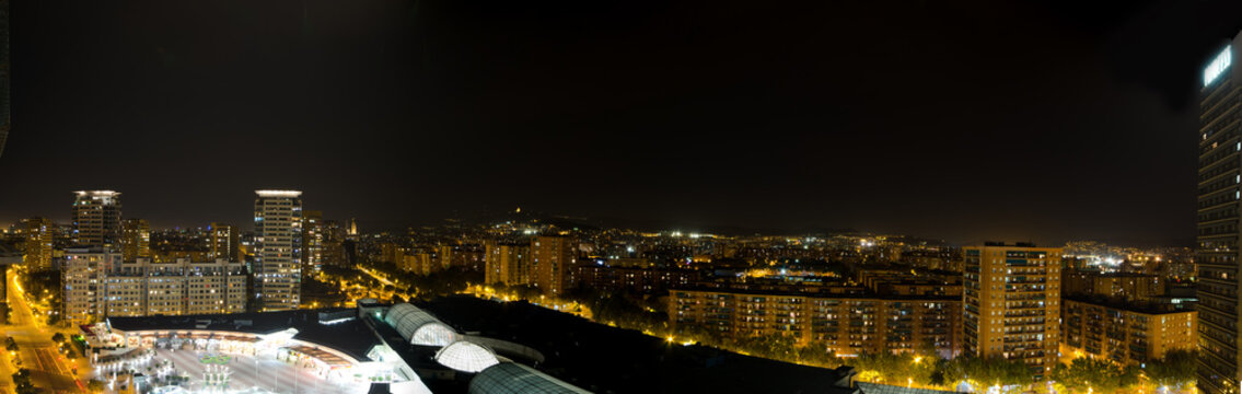 Panoramic rooftop skyline view of Barcelona by night.