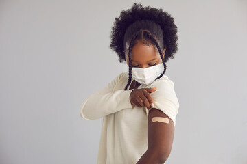 Obraz Woman receives Covid 19 vaccine injection. Young black lady showing arm with adhesive plaster bandage after getting vaccinated for coronavirus. Vaccination concept, light gray copy space background - fototapety do salonu