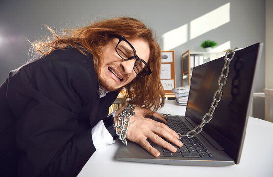 Corporate slave. Side view of a tired crazy office worker who works overtime chained to a laptop and cries. Concept of workload, extra hours and modern corporate slavery.