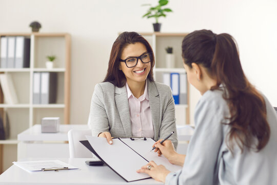 Contract signing, last formality. Smiling bank manager or recruiter hold financial document. Female client putting signature or job applicant being hired on vacant place signing employment agreement