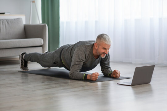 Athletic mature bearded man doing exercises at home, using laptop