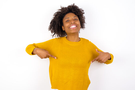 Pick me! Confident, self-assured and charismatic young beautiful African American woman wearing yellow sweater against white promoting oneself as wanting role smiling broadly and pointing at body.