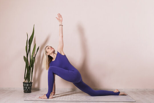 Attractive woman practicing yoga perform anjaneyasana exercise, rider pose, workout in blue sportswear