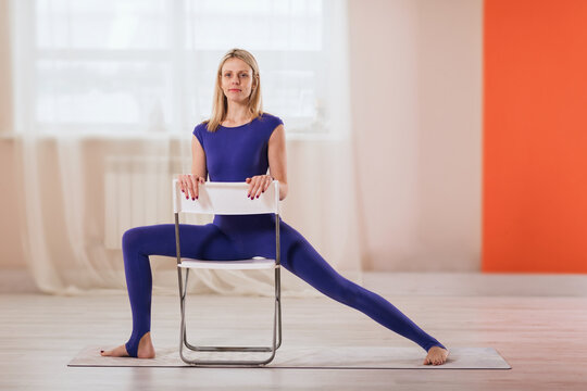 Beautiful woman blonde in blue sportswear, practicing yoga, performs a warrior's pose on a chair to relax the lower abdomen, place the hip joint in the right position, relieve the load from the back