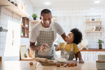 Cheerful smiling Black son enjoying playing with his father while doing bakery at home. Playful...