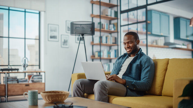 Handsome Black African American Man Working on Laptop Computer while Sitting on a Sofa in Cozy Living Room. Freelancer Working From Home. Browsing Internet, Using Social Networks, Having Fun in Flat.