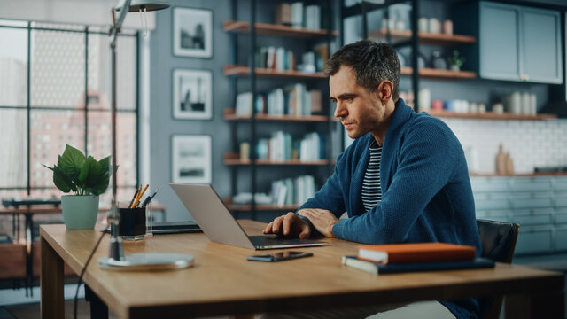 Handsome Caucasian Man Working on Laptop Computer while Sitting Behind Desk in Cozy Living Room. Freelancer Working From Home. Browsing Internet, Using Social Networks, Having Fun in Flat.