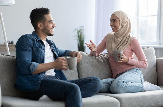 Young muslim couple drinking coffee and having conversation at home