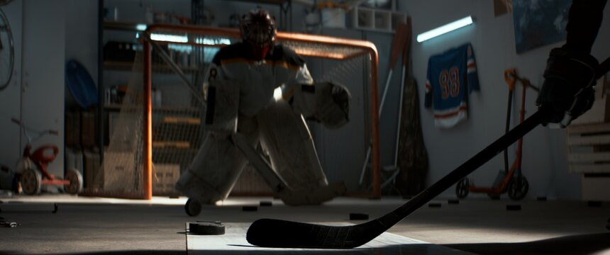 Kid boys friends or brothers practicing hockey shots inside a covered garage. Shot with 2x anamorphic lens