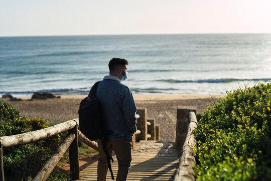 Chico joven a contra luz bajando pasarela de madera en la playa