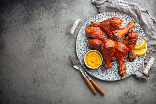 Traditional Indian dish Tandoori chicken legs served with exotic yellow sauce and lemon wedges on rustic aluminum plate on grey concrete background from above with space for text