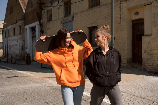 Two teenage skater girls are hanging out in the neighborhood, chatting and smiling.