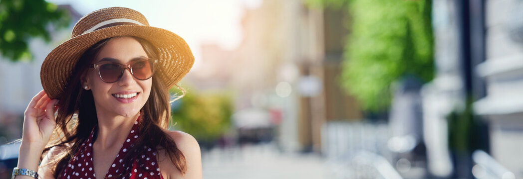 Smiling caucasian woman wearing straw hat sunglasses walking in summer city and enjoying the weather