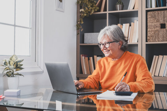 Happy old caucasian businesswoman smiling working online watching webinar podcast on laptop and learning education course conference calling make notes sit at work desk, elearning concept.