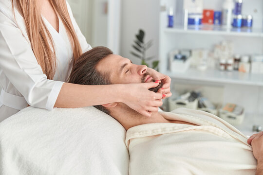 Man with beard is lying on back, getting face lifting massage. Facial massage beauty treatment. Wellness, beauty and relaxation concept
