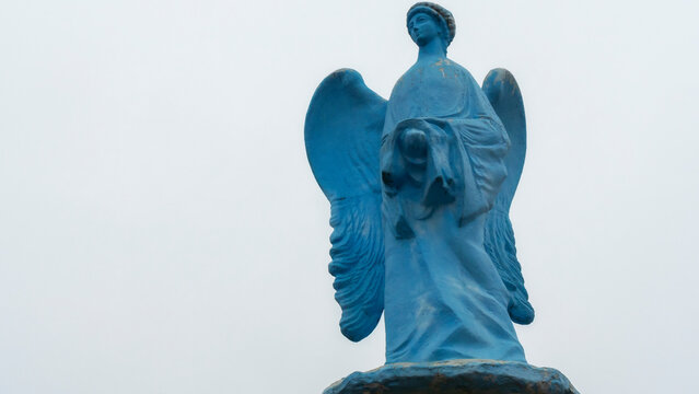 Low angle view of a transparent statue of blue angel. Religion or LGBTQ symbol. Transgender concept.