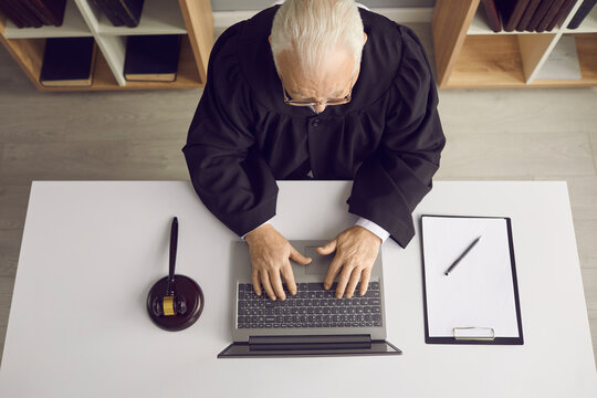 Law consultation and legal advice online: Professional senior judge, attorney or lawyer sitting at desk with laptop, doing web research or answering client's question on website. High angle from above