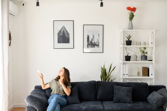 Woman sits on the couch in living room and feels hot, holds remote control switcher and turns on air conditioner, escapes from the summer heat at home under a stream of cold air from a split system