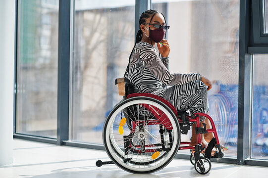Young disabled African American woman in wheelchair at home, wear face mask.