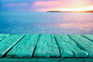 Fototapeta Sunset on the seashore and wooden table in the evening