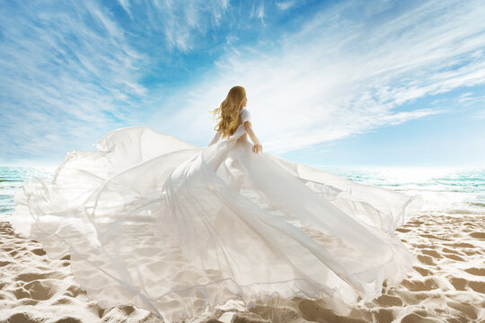 Woman on Beach in White Dress flying on Wind. Summer Vacation. Beach Sand Sea Sunshine Sky