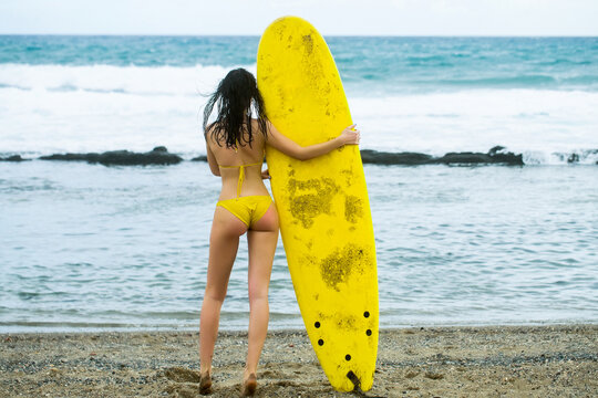 Beautiful woman surfer, sexy slim brunette in swimsuit with sporty buttocks holding yellow surfboard on sandy beach outdoors on sunny summer day near blue sea.