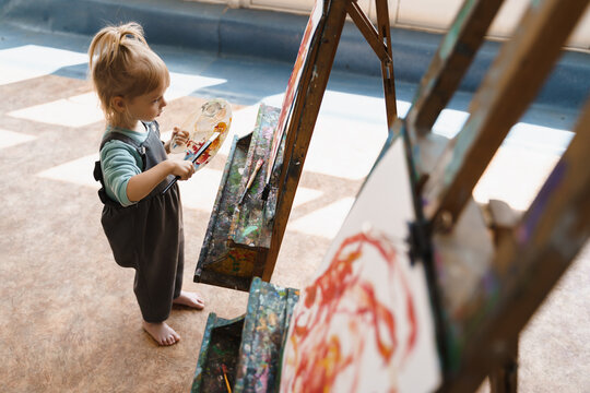 Little  girl draw a picture on an easel