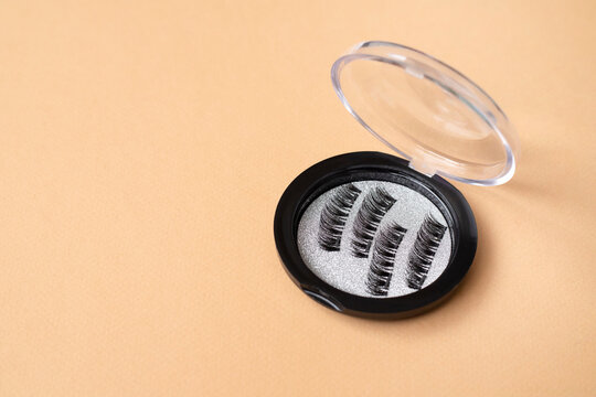 Magnetic eyelashes tool on beige background. Space for text