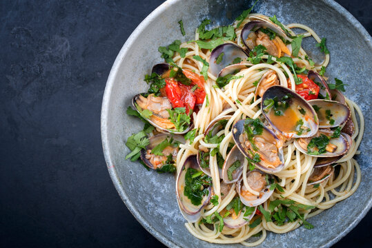 Spaghetti alle vongole with tomato in seafood jus served as top view at a Nordic design bowl with copy space left