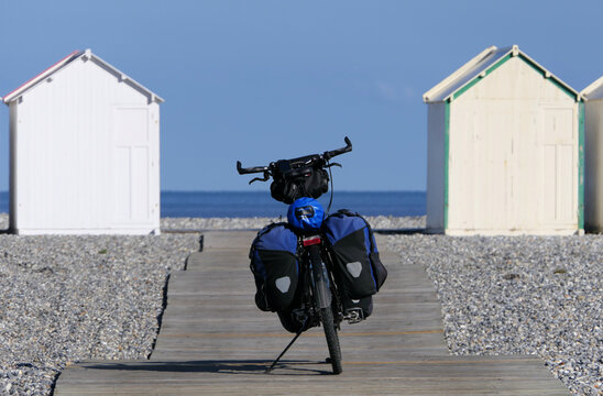 A bicycle on a boardwalk on the coast in front of white, small changing houses.