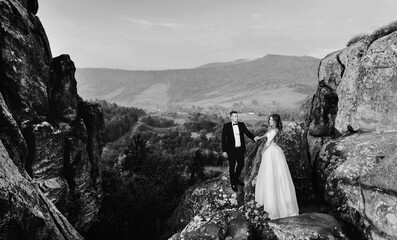 Happy husband and wife. Wedding day. Beautiful nature. Walk during the photo session. They smile at each other. Holding hands. Wall mural